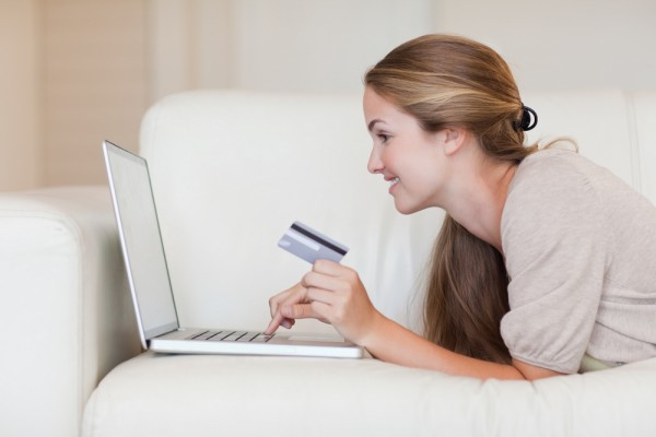 woman on sofa looking at laptop with credit card in her hand