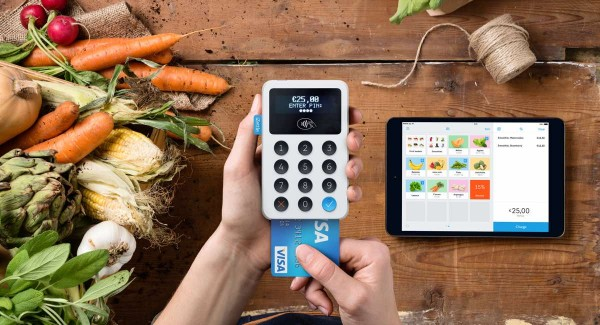 iZettle Reader held in hand with card processing and iPad on table